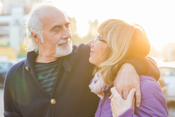 Middle age couple hugging outdoor backlight