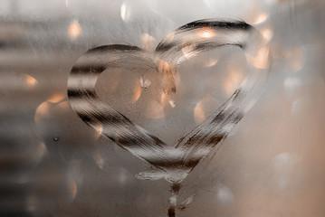 Disegno di un cuore su un vetro appannato