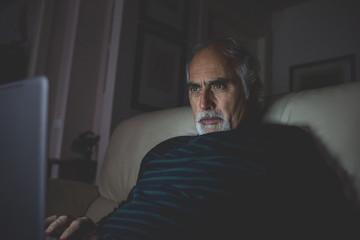 Man middle-age using notebook illuminated