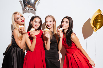 Four smiling gorgeous young women eating cupcakes on the party