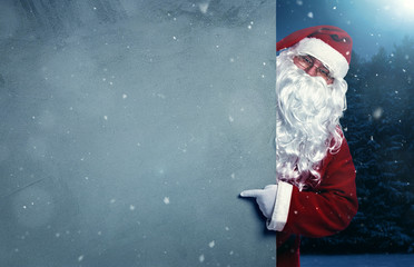 Santa Claus pointing on blank advertisement banner