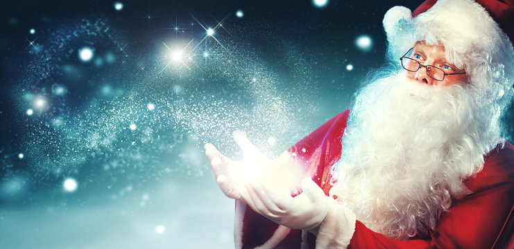 Portrait of happy Santa Claus with magic light in his hands