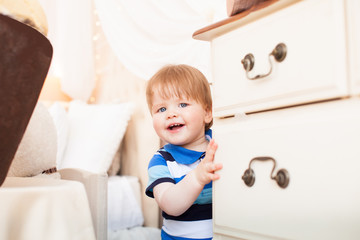 Happy little boy. Funny little boy grimacing looking from behind the cabinet