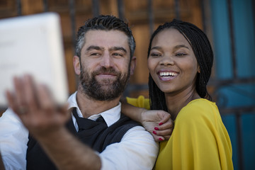 Man and smiling woman taking a selfie with tablet