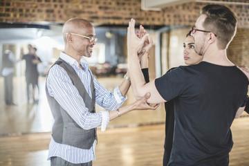 Dance instructor leading couple in dance studio