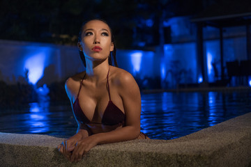 Beautiful sensual Asian woman in sexy bikini with wet hair standing in the water with hands on the edge of swimming pool during summer evening over amazing blue lights background