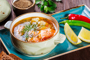 Fish soup with salmon and shrimps, dill, potatoes, lemon, peppers and bread on dark wooden background, healthy food. Top view