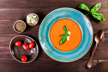 Tomato gazpacho soup with basil, feta cheese, ice and bread on dark wooden background, Spanish cuisine. Ingredients on table. Top view
