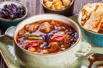 Soup with meat, oregano, chickpeas, peppers and vegetables served with crackers and bread on plate on dark wooden background. Homemade food. Ingredients on table. Top view