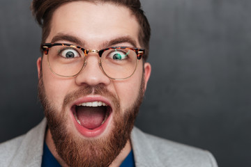 Surprised happy young businessman in glasses with opened mouth
