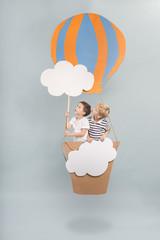 Children sitting in balloon basket