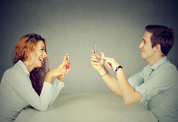 man woman using mobile phones texting taking pictures