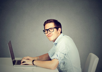 Nerdy man using a laptop computer