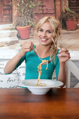 Young female eating spaghetti. Italian traditional food.