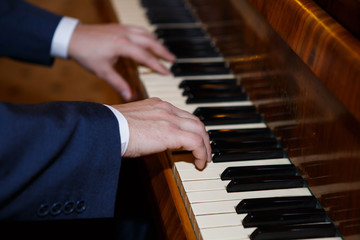 Pianist hands playing the piano. Classical music keyboard. Musician in concert performing music on a stringed percussive musical instruments.
