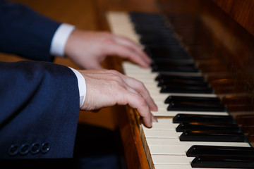 Pianist hands playing the Grand piano. Classical music keyboard. Musician in concert performing music on a stringed percussive musical instruments.