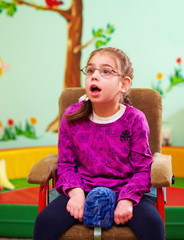 cute girl in wheelchair in kindergarten for children with special needs