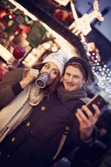 Pärchen auf dem Weihnachtsmarkt macht ein Selfie