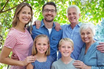 Smiling family standing against tree