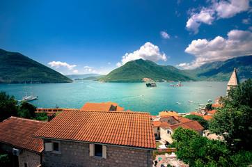Harbor and ancient buildings in sunny day at Boka Kotor bay (Boka Kotorska), Montenegro, Europe. .