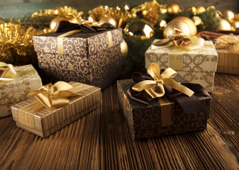 Golden Christmas decoration. Presents in boxes on a wooden background with copy space. Golden baubles. Christmas theme. Golden and brownish aesthetics. Christmas spices.