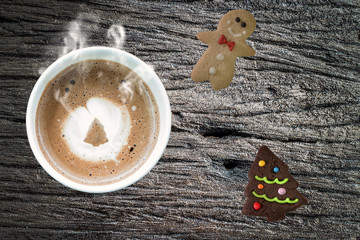 Coffee cup and gingerbread cookies on wooden table