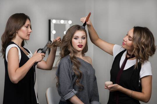 Makeup and hairstyle process. Makeup artist and hairdresser work in tandem, curl and color model in the salon. Three beautiful women