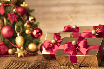 Golden presents with red ribbon under christmas tree. Wooden background and table. Red and gold. Place for typography and logo. Copy space.