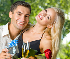 young happy couple with gift and rosa, outdoors