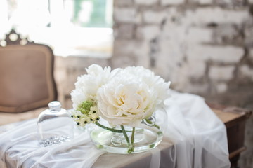 Vase with beautiful David Austin roses on a table. Nice rare white flowers for rustic wedding decoration. Loft style. Fresh bouquet for bride. Blurred background.
