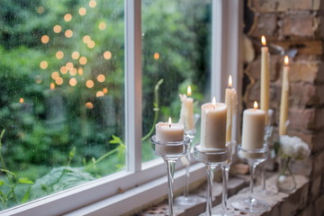 White candles in glass holders. Beautiful rustic wedding decoration. Candle light reflecting in window. Loft style wedding. Blurred background