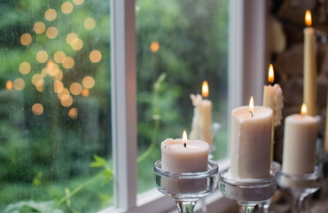 White candles in glass holders. Beautiful rustic wedding decoration. Candle light reflection in window. Loft style wedding. Blurred background
