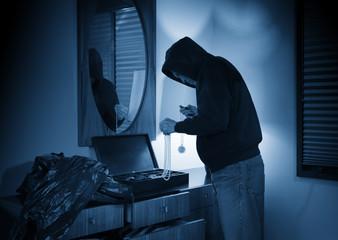 Hooded burglar ransacking a jewelry box in a home - fototapety na wymiar