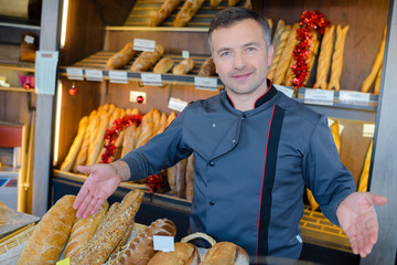bakery shopkeeper is proud of his bread production