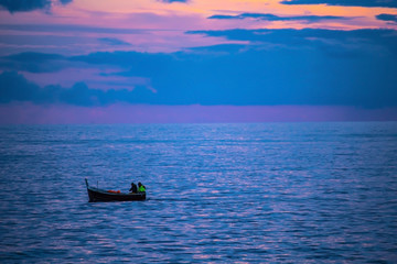 Small boat on the sea with sunset sky