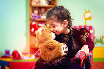 cute little girl in wheelchair hugging plush bear in kindergarte