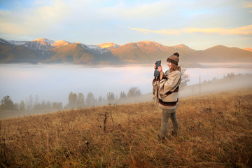 Woman hiker taking photo with tablet at mountain peak. Early morning. Misty mountain. Young girl over the clouds in the valley looking at calm autumn sunrise. Woman in boho style.