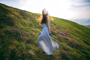 Young woman in a dress running to the sun in the mountains. Young girl in the mountains. Defocus