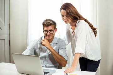 Male and female colleagues using laptop at office