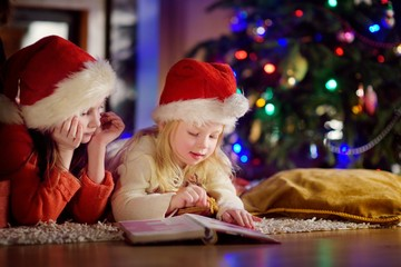 Two cute little sisters reading a story book together under a Christmas tree