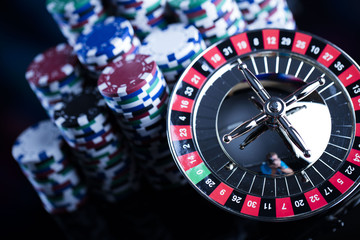 Casino theme. High contrast image of casino roulette, poker game, dice game, poker chips on a gaming table, all on colorful bokeh background. Place for typography and logo.