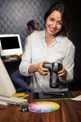 Creative businesswoman looking at pictures on camera