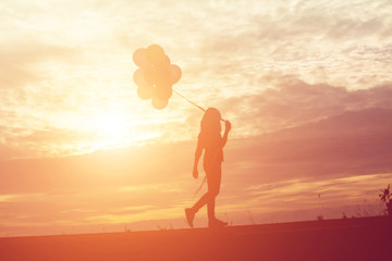 silhouette of young woman holding colorful of balloons with suns