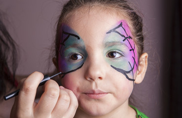 Make-up artist working with a little girl before halloween party