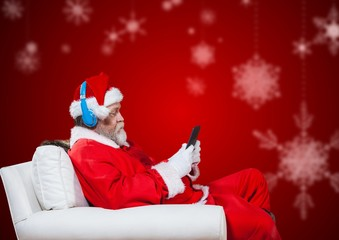 Santa claus sitting on chair and using mobile phone