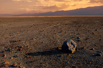 Wall Mural - A lone boulder lies in an expansive, empty desert at sunset