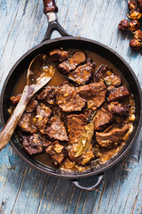 Beef stewed cast iron. Meat Stew of beef with caramelized onion. Overhead of Roasted beef meat.