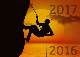Composite image of 2017 with silhouette of man climbing a cliff