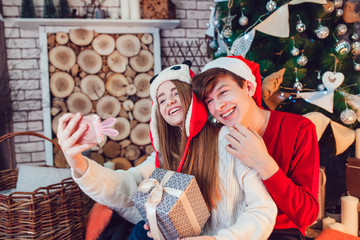 Young couple in love sitting near christmas tree in funny hats having fun and make selfie. New Year