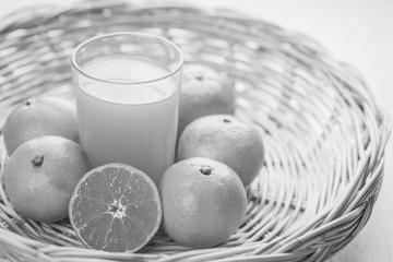 Glass of orange juice a wicker basket , black and white